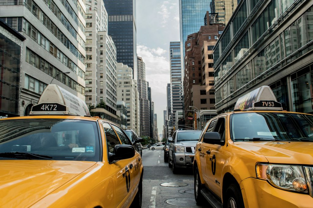 Image of street in New York City with 2 taxi cabs waiting for a light to change. Background shows buildings, including a McDonald's sign visible in the distance.